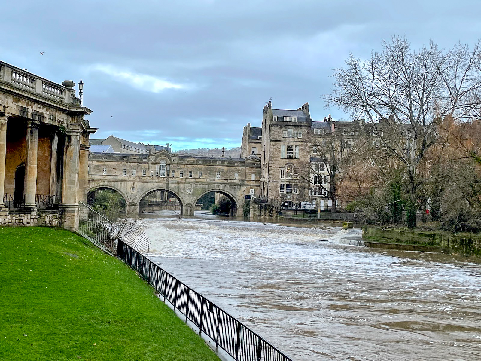 A view from Parade Gardens of the River Avon in Bath flows over the wier with Pulteney Bridge in the background