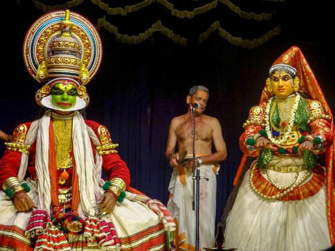 Kathakali performer with Pachcha (green) makeup, a musician upstage and a Minikku perfomer with yellow makeup at Varkala Cultural Center, Kerala, India