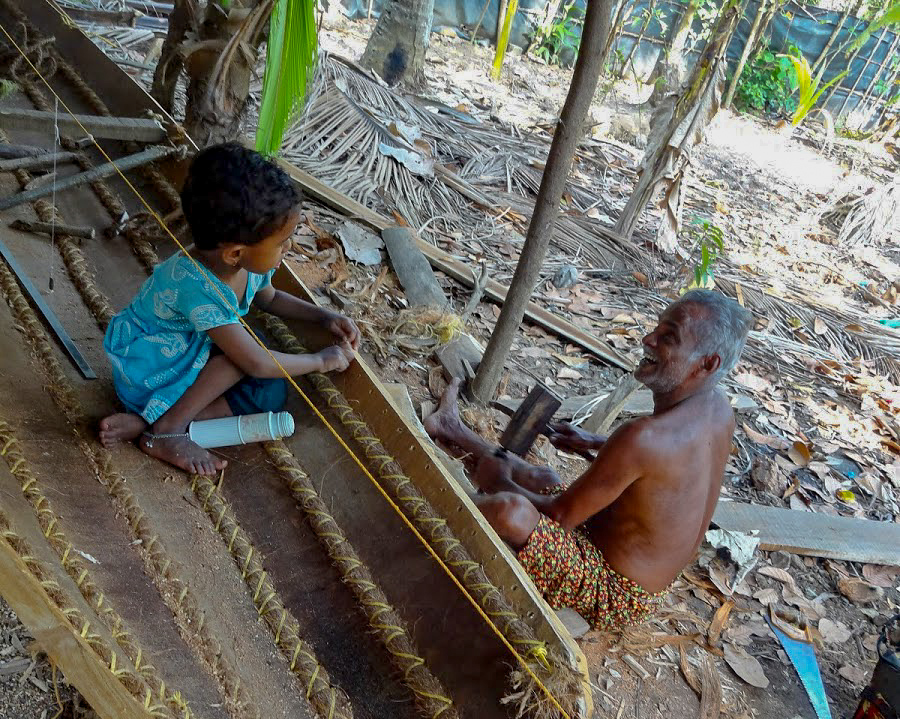 a young Indian boy sits in a wooden boat, as an older Indian man works on it with a mallet, Kerala, India