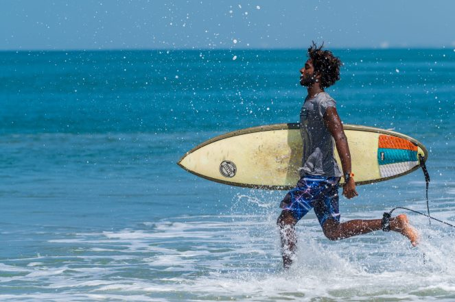 An Indian male surfer with his yellow surfboard running in the Laccadive Sea, Varkala, India