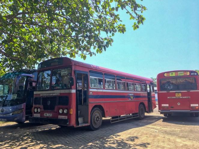 2 red Lanka Ashok Leyland buses at a bus station in Sri Lanka