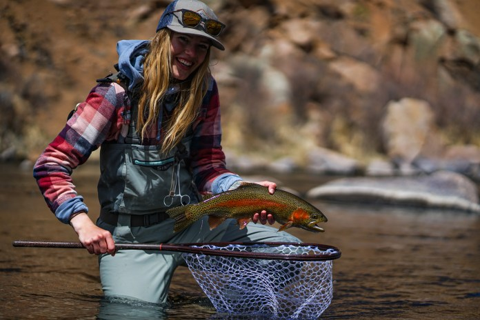 An anglers holds a beautiful Rainbow Trout caught on the South Platte River in Colorado
