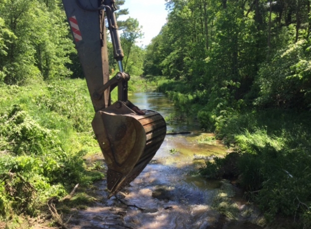 Construction equipment dredging a creek