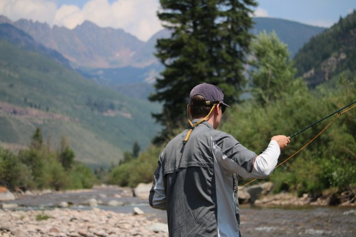 Person casting on Gore Creek with mountains in the background.