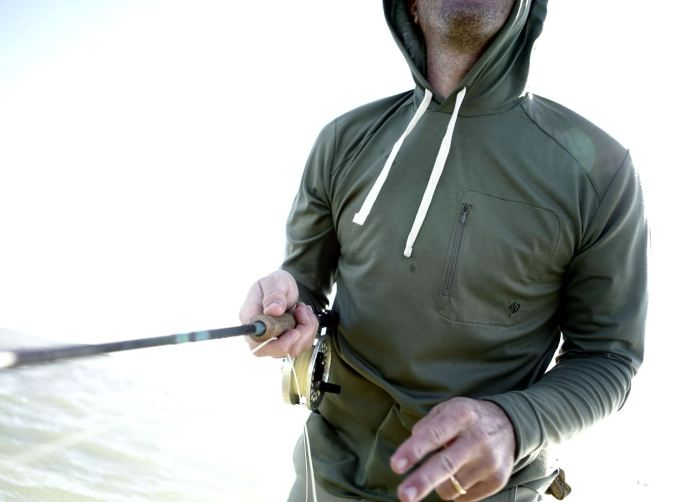 guy fishing wearing duck camp hoodie