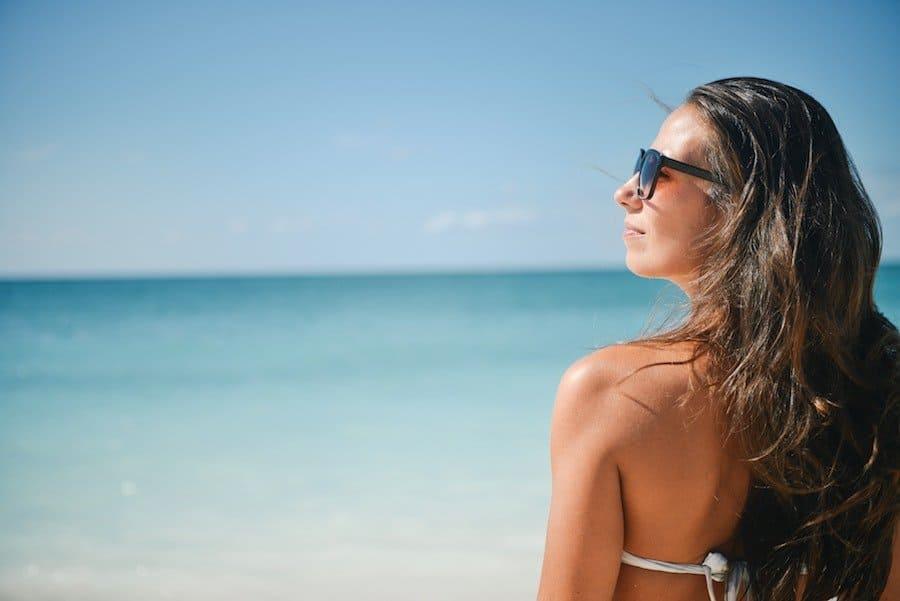 Bikini clad brunette girl looking out to the ocean | Bali beach club | flystayluxe.com