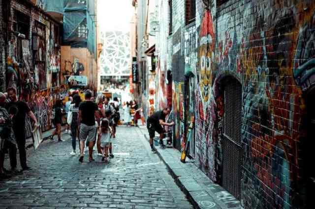 Hosier Lane in Melbourne. People walking down the laneway watching graffiti street artists at work.