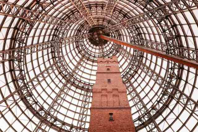 Melbourne Central shopping centre. An old red brick building house inside a glass and steel dome structure.