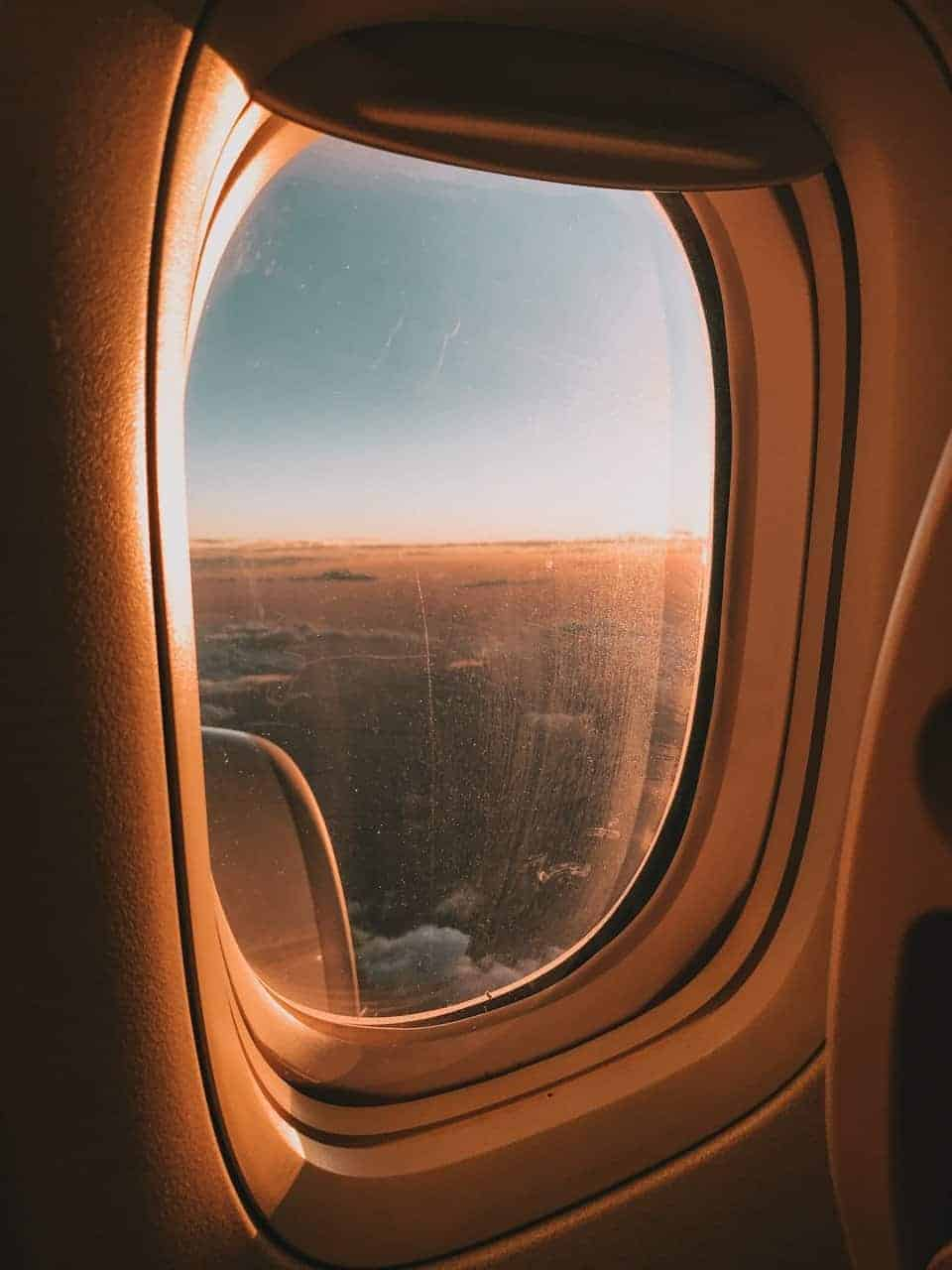 View from airplane window seat overlooking the ocean at sunset