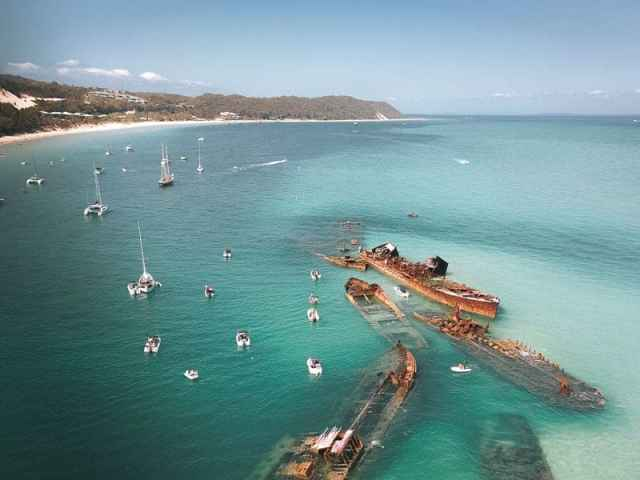 Tangalooma Wrecks on Moreton Island are a spectacular formation of shipwrecks located just off the coast of Brisbane, Queensland Australia. It's possible to go camping on the beaches, see dolphins and whales or visit on a day trip #MoretonIsland #Australia #Queensland #DayTrip #thingstodo #Tangalooma