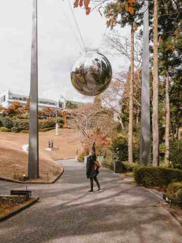 A large silver ball exhibit at the Hakone Open Air Museum