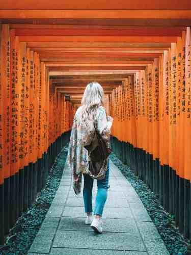 A girl walks through the orange torii gates at Fushimi Inari Shrine in Kyoto, Japan