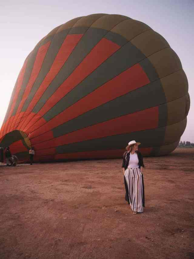 Ready to take flight in Morocco: A stylish girl wanders in front of a hot air balloon being filled with air.
