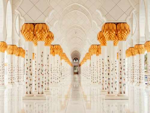 White marble hallways of the Sheikh Zayed Grand Mosque with gold leaf trim