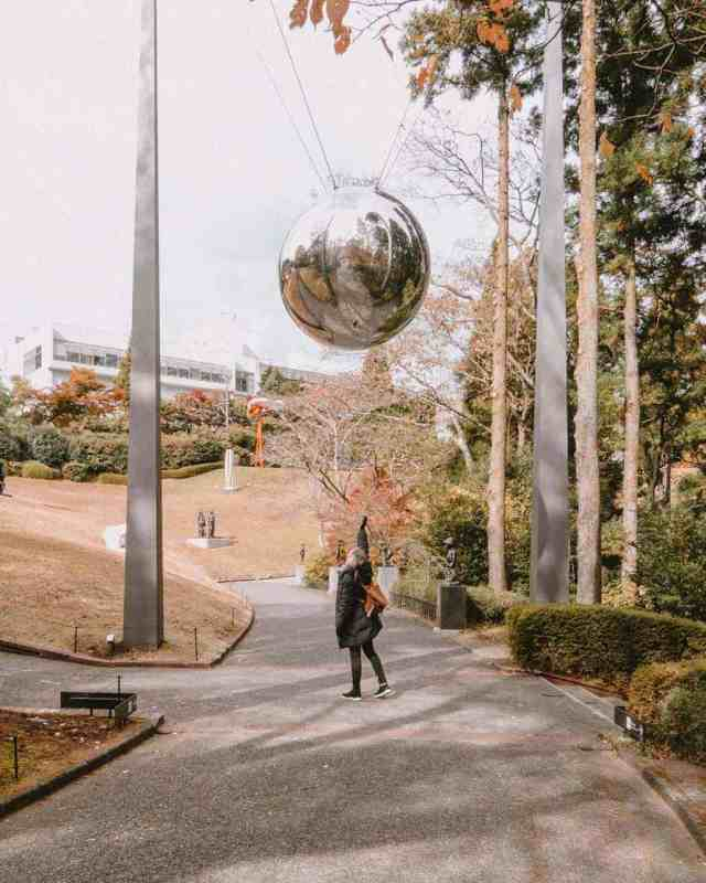 Girl reaching overhead to one of the exhibits in the Hakone Open Air Museum, Japan