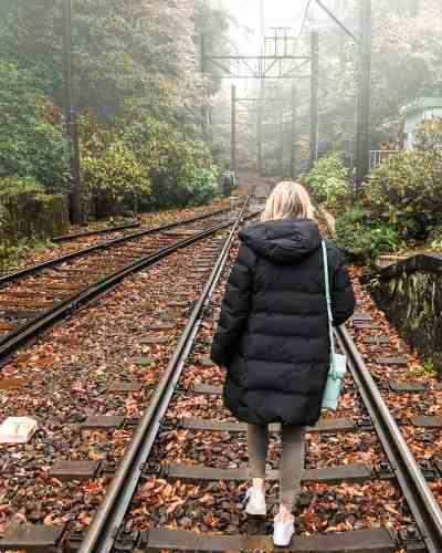 Girl walking along the Hakone Tozan railway line on a misty fall morning