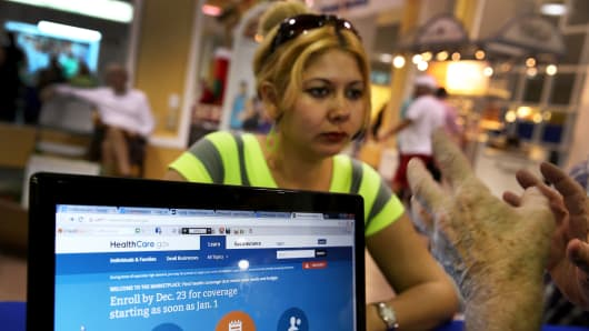 A woman sits with an insurance agent as she inquires about purchasing health insurance under the Affordable Care Act at a kiosk at the Mall of the Americas on Dec. 22, 2013 in Miami.