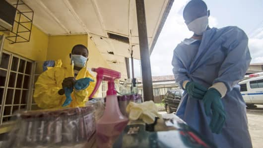 Medical staff put on protective gear at Kenema Government Hospital before taking a sample from a suspected Ebola patient in Kenema, Sierra Leone.