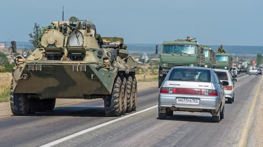 A Russian armored personnel carrier leads a column of military trucks as they leave the Russian-Ukrainian border area outside of Kamensk-Shakhtinsky, Russia.