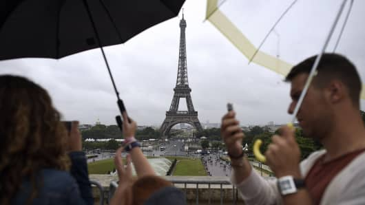 Tourists take pictures under the rain in front of the Eiffel Tower in Paris.