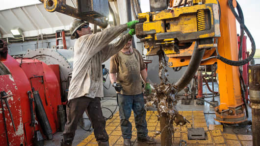 Workers line up pipe while drilling for oil in the Bakken shale formation outside Watford City, N.D.