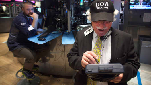 """Trader Peter Tuchman wears a """"Dow 18,000"""" cap as he works on the floor of the New York Stock Exchange in New York, December 23, 2014."""