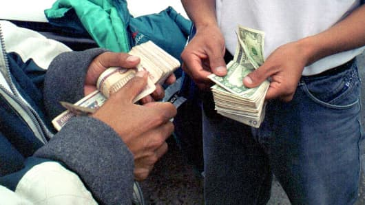 A man buys U.S. dollars from a street money changer at the rate of 25,000 sucres to the dollar in Quito, Ecuador, Jan. 11,2000, after the directors of Ecuador's Central Bank approved a plan to dollarize the economy.