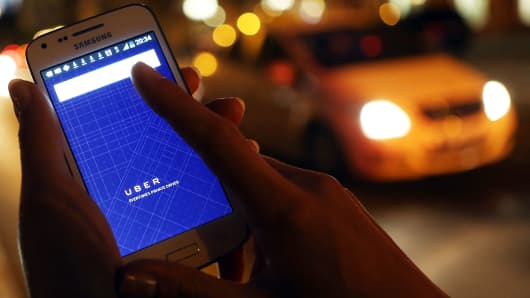 A woman uses the Uber app on a smartphone as a taxi cab drives by.