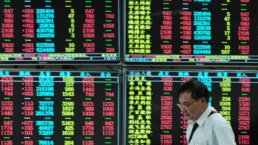 An investor observes stock market at a stock exchange hall in Jiujiang, China.