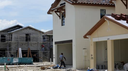 Plasterers stand on scaffolding, back, while a worker walks into the garage of a home under construction at the Lennar Corp. Madison Pointe at Central Park development in Doral, Florida.