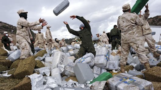 Mexican soldiers unload bundles of seized marijuana before incinerating the drugs at a military base in Tijuana, Mexico.