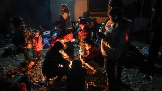 Migrants and refugees gather around a bonfire as they wait to enter a refugee camp after crossing the Greek-Macedonian border.