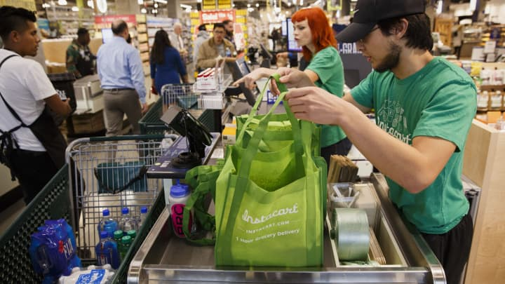 InstaCart employees fulfill orders for delivery at a Whole Foods Market store in Los Angeles.