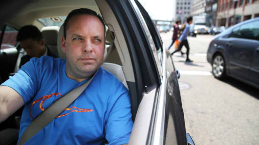 Uber driver Dean Johnson poses for a portrait while working outside South Station in Boston on April 22, 2016.