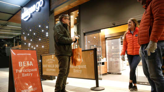 Amazon employees are pictured outside the Amazon Go brick-and-mortar grocery store without lines or checkout counters, in Seattle Washington, U.S. December 5, 2016.