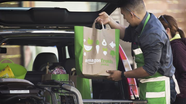 An employee loads bags of groceries into a customer's vehicle at an AmazonFresh Pickup location in Seattle, Washington.