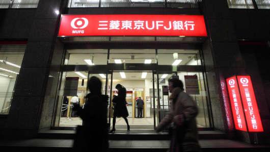 Pedestrians walk past a Bank of Tokyo Mitsubishi UFJ branch in Tokyo, Japan, on Thursday, Jan. 15, 2009.