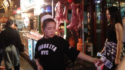 A worker at one of many food vendors in the Muslim Quarter of Xi'an, China.