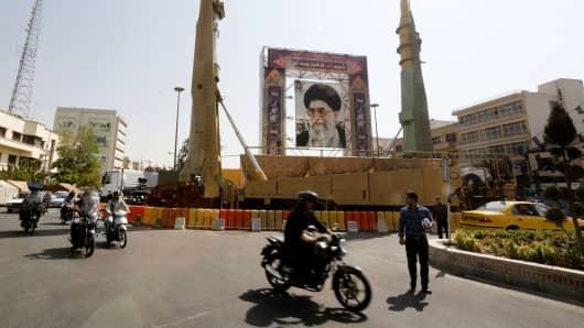 Iranians walk past Sejjil (L) and Qadr-H medium range ballistic missiles displayed next to a portrait of Iranian Supreme Leader Ayatollah Ali Khamenei on September 25, 2017, on Baharestan square in Tehran.