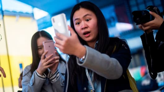 A Chinese woman reacts while setting up the facial recognition feature on her iPhone X inside an Apple showroom in Beijing on November 3, 2017.