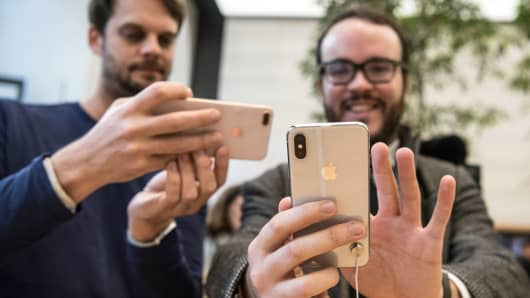 A member of staff photographs a customer as he checks the new iPhone X upon its U.K release in the Apple store, on November 3, 2017 in London, England.