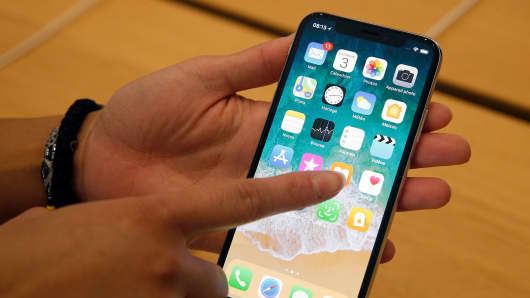Apple s new iPhone prices likely higher than Wall Street expects A customer holds an Apple iPhone X  the new model of Apple smartphone at the