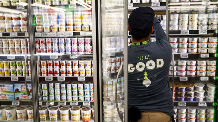 An employee stocks yogurt for sale on the opening day of the 365 by Whole Foods Market store in the Silver Lake neighborhood of Los Angeles, California