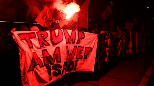 A flare is lit as people protest against the attendance of the US president to the upcoming Davos World Economic Forum, on January 23, 2018, in central Zurich.