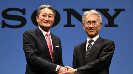 Sony president and CEO Kazuo Hirai (L) shakes hands with executive deputy president and CFO, Kenichiro Yoshida (R), during a press briefing at the company's headquarters in Tokyo on February 2, 2018. Sony chief executive Kazuo Hirai, who led a major and successful overhaul at the Japanese electronics giant, will step down at the end of March, the firm said on February 2 and will become Sony chairman.