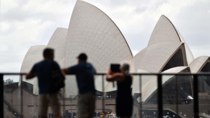 Οι τουρίστες φωτογραφίζουν την Όπερα του Σίδνεϊ στο Σίδνεϊ της Αυστραλίας στις 13 Φεβρουαρίου 2018. Η Credit Suisse ανέδειξε τον τουριστικό τομέα ως ευκαιρία στην αυστραλιανή αγορά.