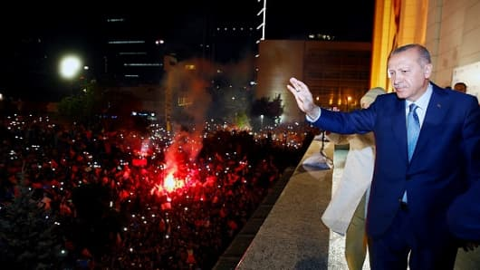 President of Turkey and leader of the Justice and Development Party (AK Party) Recep Tayyip Erdogan greets the crowd from the balcony of the ruling AK Party's headquarters following his election success on June 25, 2018. Photo by Kayhan Ozer/Anadolu Agency/Getty Images)