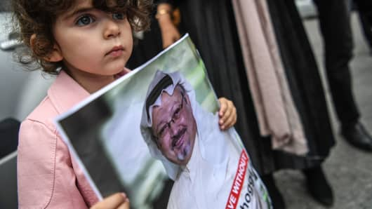 A girl holds a picture of missing journalist Jamal Khashoggi during a demonstration in front of the Saudi Arabian consulate on October 8, 2018 in Istanbul.