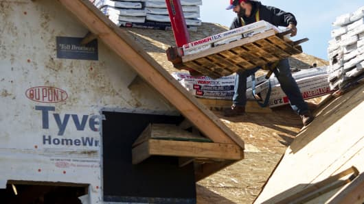 A contractor stacks roofing materials while working at a home under construction at the Toll Brothers community at Bowes Creek Country Club in Elgin, Illinois.
