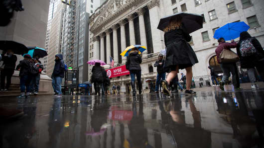 Pedestrians carrying umbrellas walk past the New York Stock Exchange.